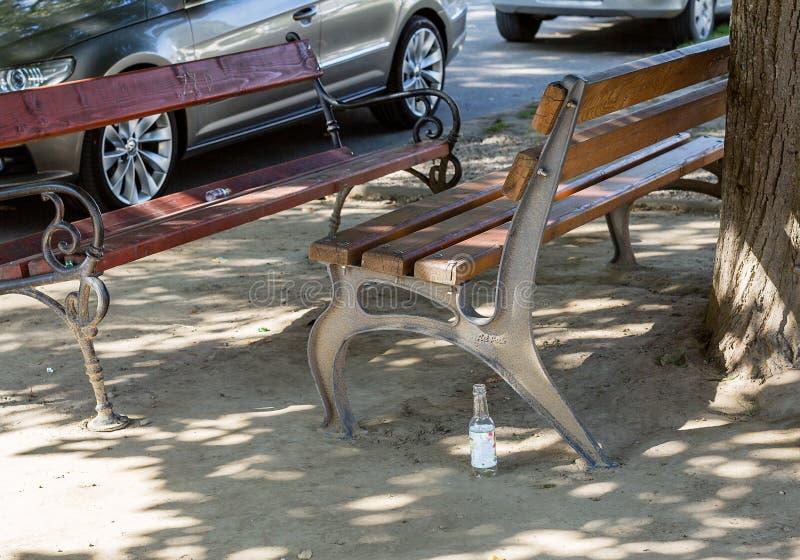 Una bottiglia di vetro vuota ha lasciato vicino al banco nella via Stile di vita, abitudini di passione, concetto di comportament fotografia stock