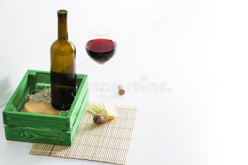 Una bottiglia di vino rosso con un vetro e un pezzo di formaggio fotografia stock