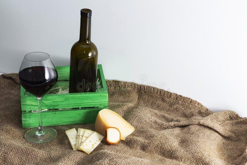 Una bottiglia di vino rosso con un vetro e un pezzo di formaggio fotografia stock libera da diritti
