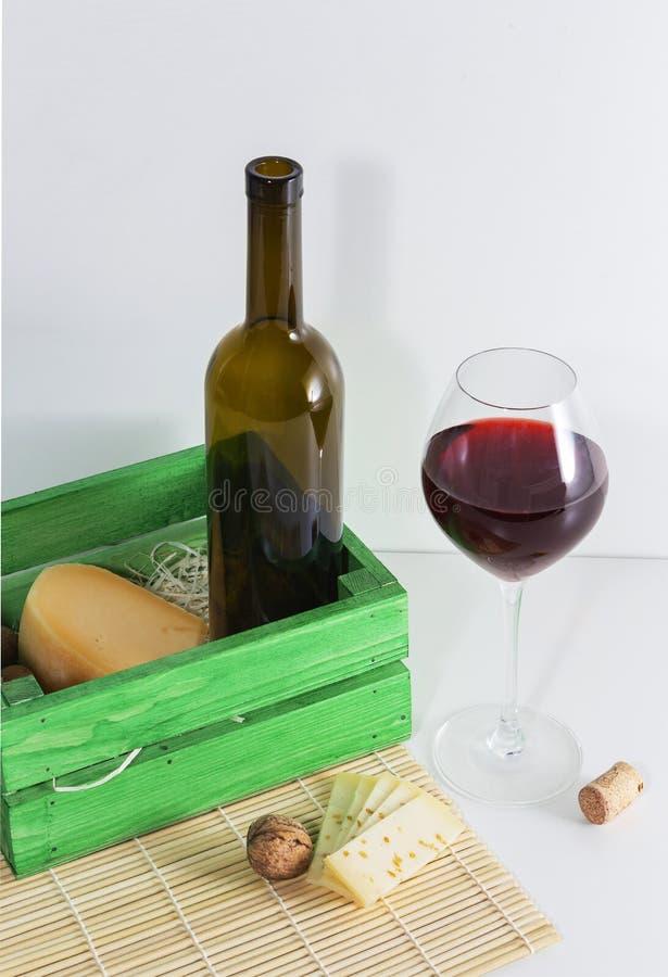 Una bottiglia di vino rosso con un vetro e un pezzo di formaggio immagine stock libera da diritti
