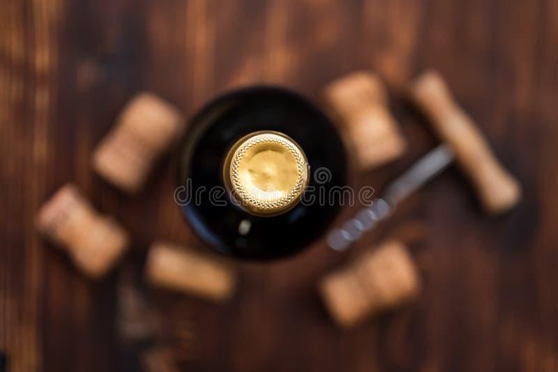 Una bottiglia scura di vino accanto a confuso una cavaturaccioli e sugheri su un fondo di legno immagine stock