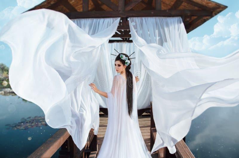 Una bruja hermosa defiende en el fondo de un gazebo de madera el agua, con un vestido blanco del aire En la imagen foto de archivo libre de regalías
