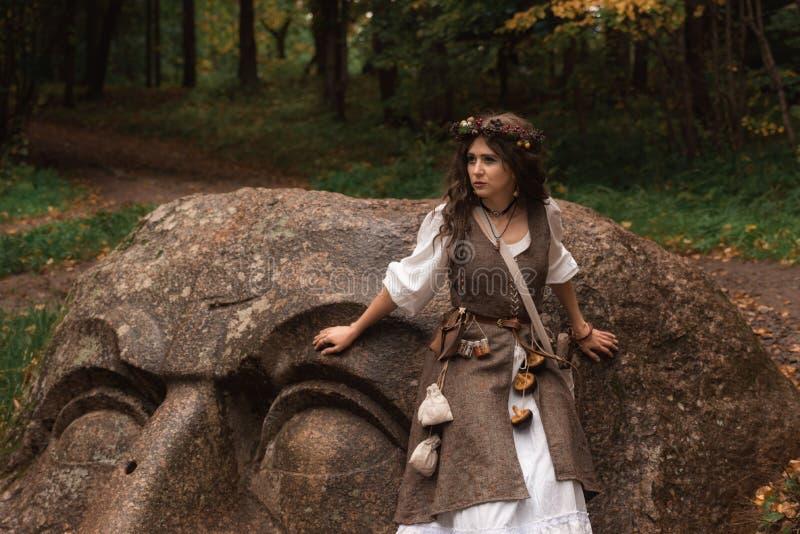 Una bruja joven en bosque foto de archivo