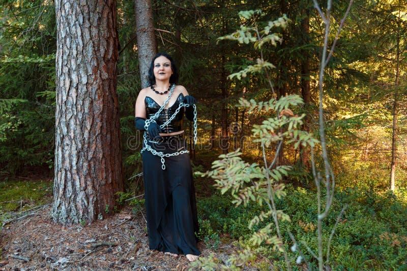 Una bruja joven en el bosque encadenado a un árbol Víspera de Todos los Santos fotos de archivo libres de regalías