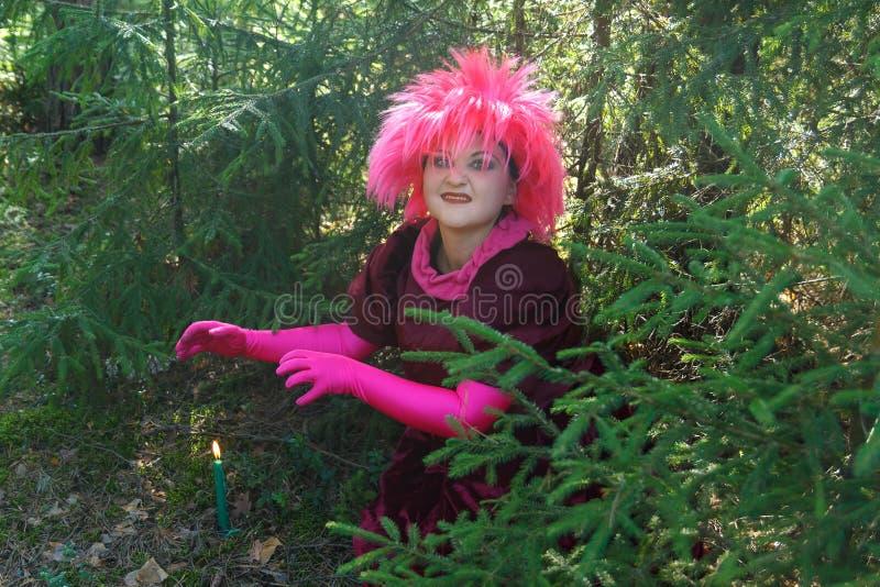 Una bruja joven en ropa púrpura conjura una vela cavada en la tierra Foto horizontal foto de archivo libre de regalías