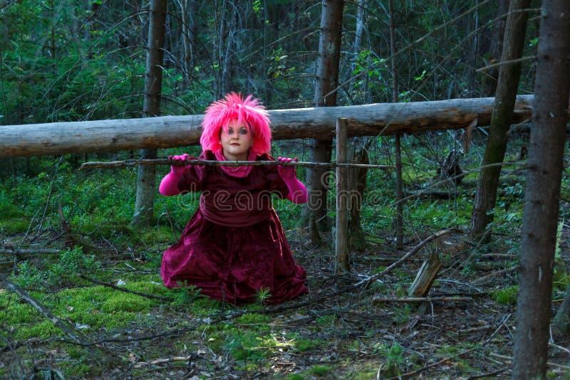Una bruja joven en ropa p?rpura en el bosque conjura una rama seca de un ?rbol imagen de archivo