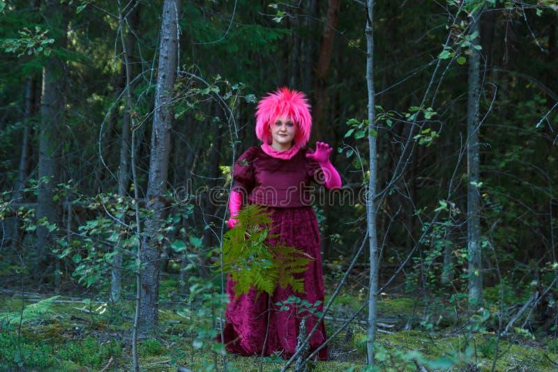 Una bruja joven en ropa púrpura realiza un ritual mágico con un helecho en el bosque foto de archivo