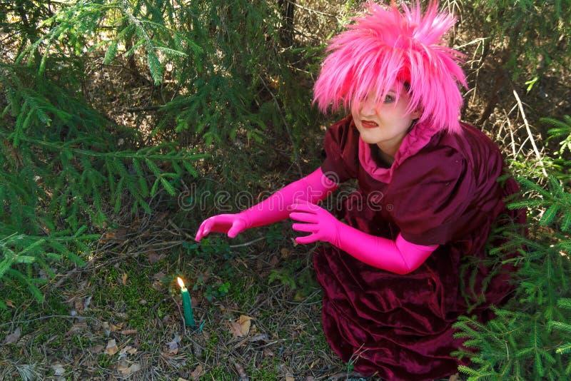 Una bruja joven en ropa p?rpura conjura una vela cavada en la tierra Foto horizontal imagen de archivo libre de regalías