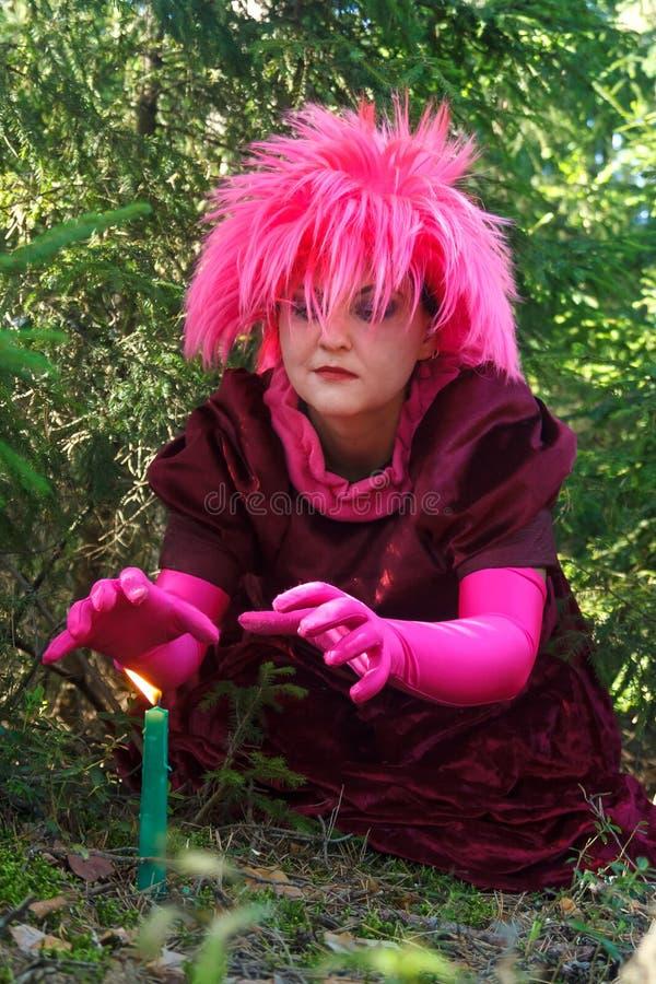 Una bruja joven en ropa p?rpura conjura una vela cavada en la tierra imágenes de archivo libres de regalías