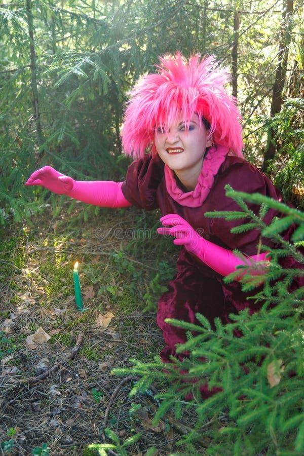Una bruja joven en ropa p?rpura conjura una vela cavada en la tierra imagenes de archivo