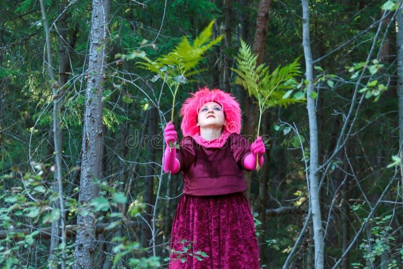 Una bruja joven en ropa p?rpura realiza un ritual m?gico con un helecho en el bosque imagen de archivo libre de regalías