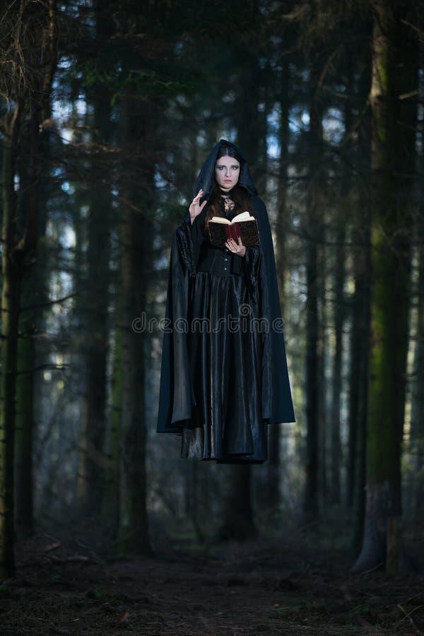 Una bruja que celebra los encantos del libro fotografía de archivo libre de regalías