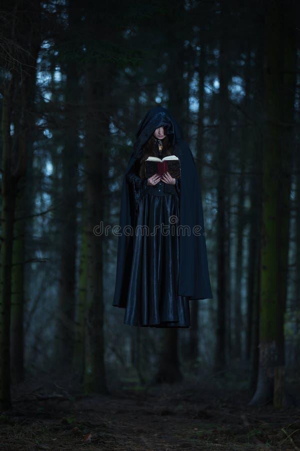 Una bruja que celebra los encantos del libro imágenes de archivo libres de regalías