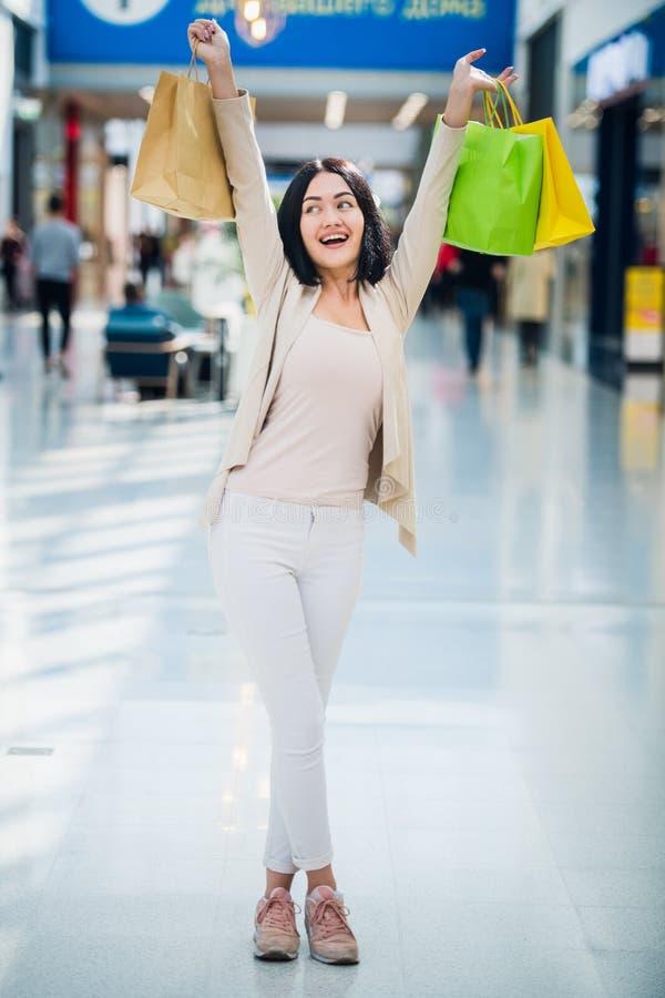 Una bruna che indossa i colori smorzati e delicati tiene i sacchetti della spesa colourful e modellati cammina ad un'esclusiva fotografia stock
