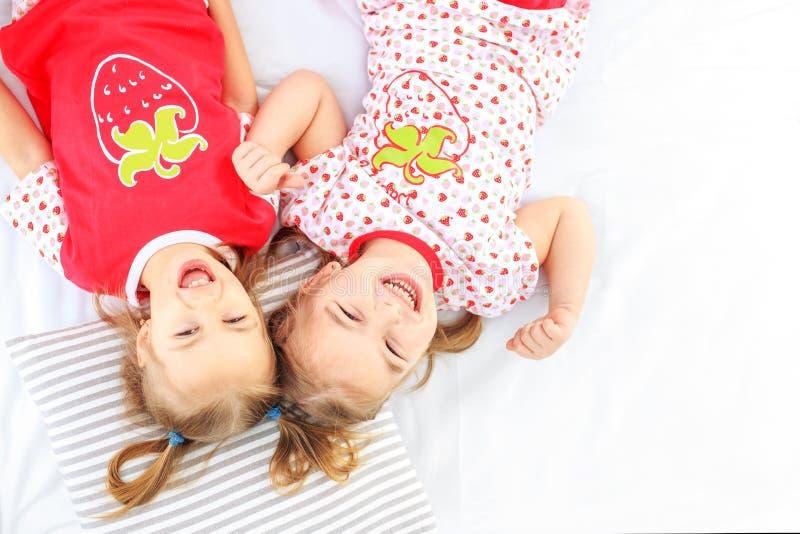 Una bugia di due bambini in un letto dei pigiami Copi lo spazio Il concetto del Ch fotografia stock