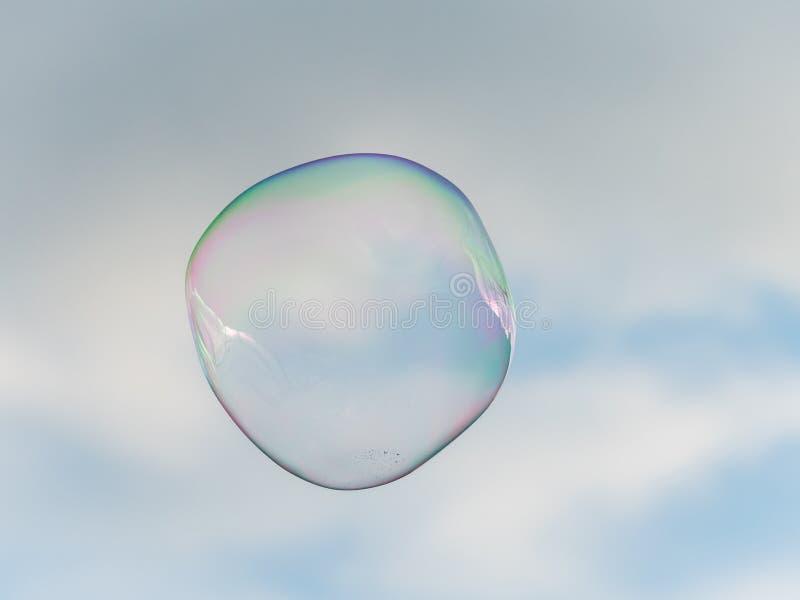 Una burbuja de jabón grande delante del cielo en parte nublado imagenes de archivo