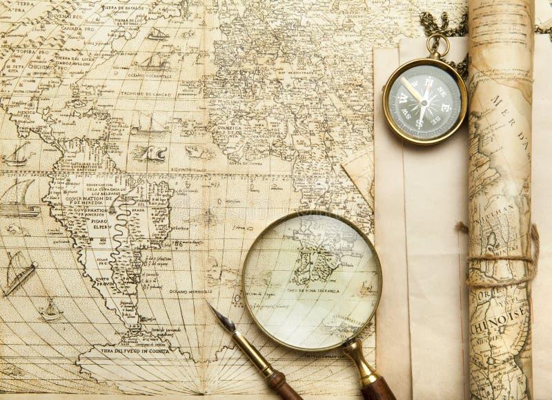 Una bussola d'ottone su un vecchio fondo della mappa immagini stock libere da diritti