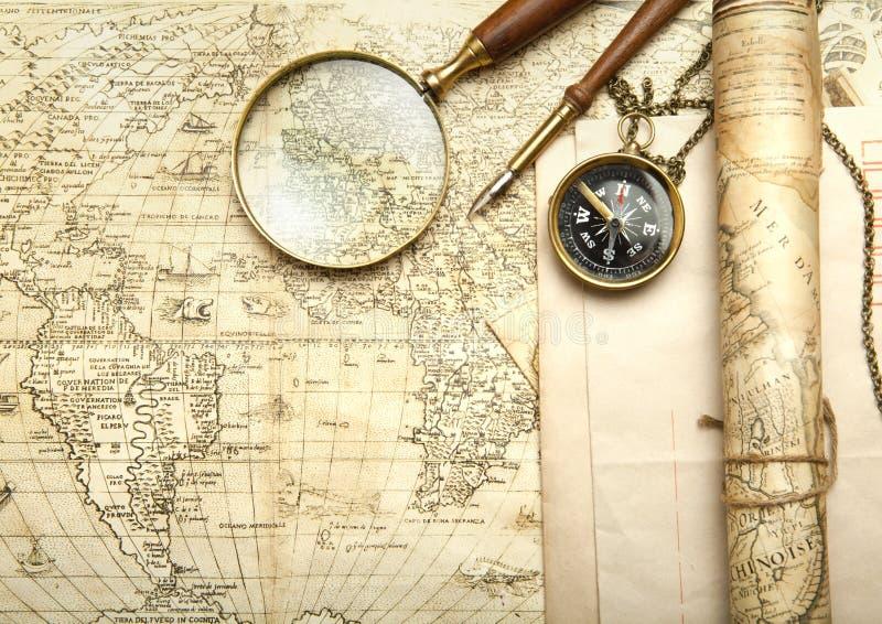 Una bussola d'ottone su un vecchio fondo della mappa immagini stock