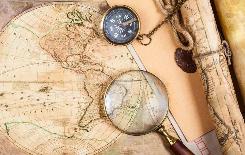 Una bussola d'ottone su un vecchio fondo della mappa fotografie stock libere da diritti