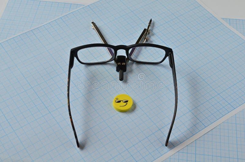 Una bussola, occhialini e una gomma gialla su carta grafica per disegnare immagine stock