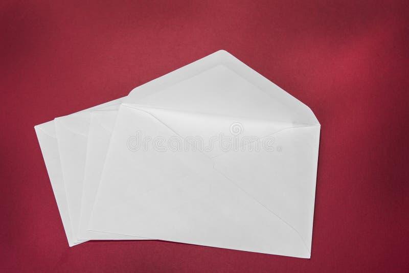 Una busta bianca aperta sui precedenti rossi fotografie stock