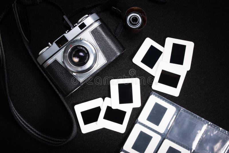 Una cámara de la película del vintage con un rollo de la película y de diapositivas numerosas imágenes de archivo libres de regalías