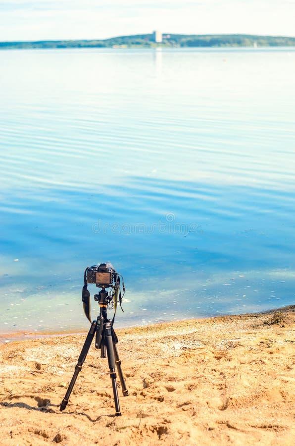 Una cámara en un trípode en la playa arenosa imagenes de archivo