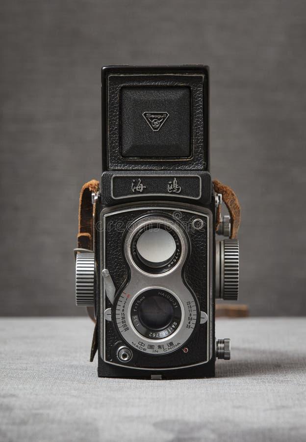 Una cámara refleja de la lente del gemelo de la gaviota 4 TLR con la correa marrón con un fondo gris, Nottingham, Reino Unido - e foto de archivo libre de regalías