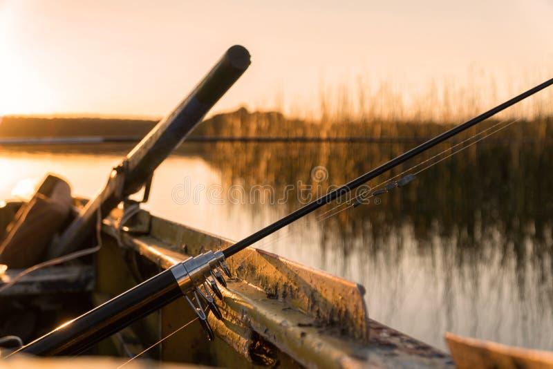 Una caña de pescar quebrada miente en el lado del barco en la puesta del sol fotografía de archivo libre de regalías