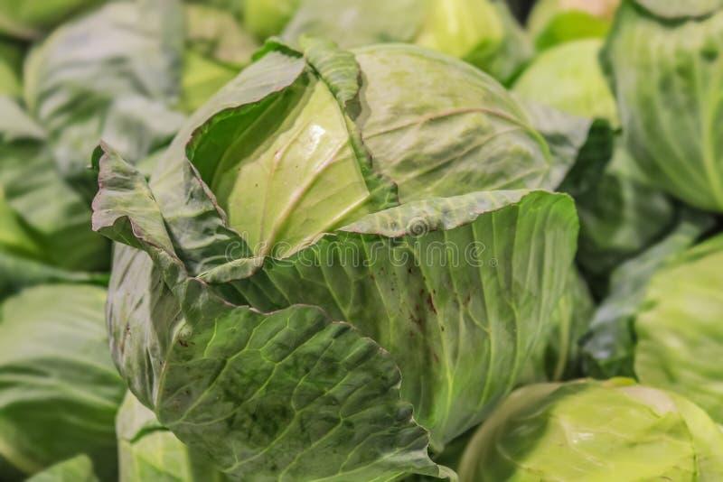 Una cabeza de la col verde crujiente con el exterior se va encima de una pila de coles verdes - foco selectivo fotografía de archivo