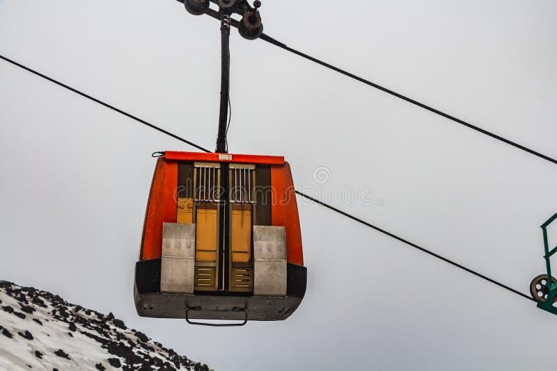 Una cabina roja de los teleféricos con a puerta cerrada debajo de la montaña vulcan negra el Etna con la nieve blanca en el fondo fotos de archivo libres de regalías