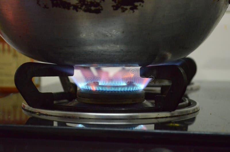 Una cacerola de aluminio debajo de las llamas en estufa de gas; el cocinar del viejo estilo fotografía de archivo