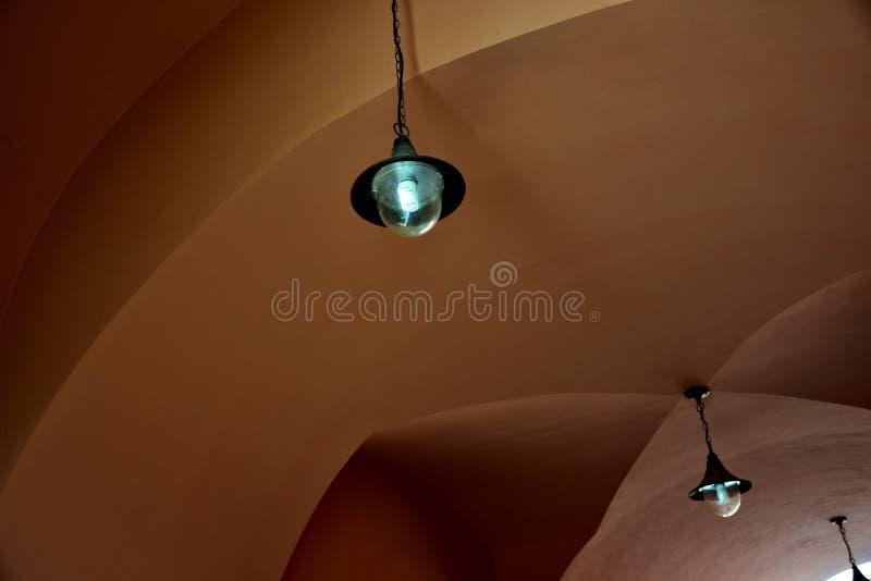 Una caduta d'annata di due stylelamps sul soffitto arcato di terracota fotografia stock libera da diritti