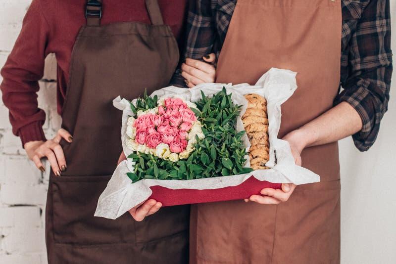 Una caja de flores y de galletas en las manos de un par joven de hombres y de mujeres foto de archivo libre de regalías