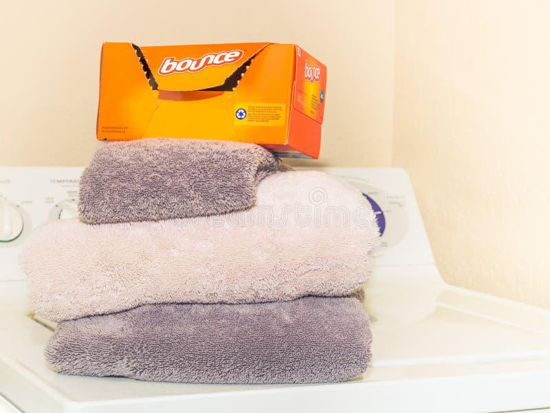 Una caja de hojas del secador de la despedida se coloca en las toallas dobladas limpias - vista delantera imagen de archivo