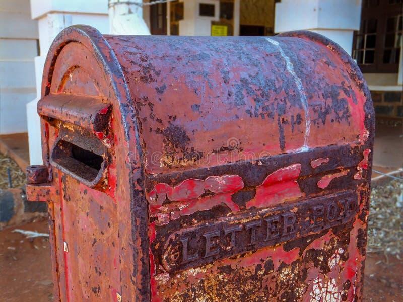 Una caja de letra roja vieja oxidada hecha sólidamente del hierro fotos de archivo