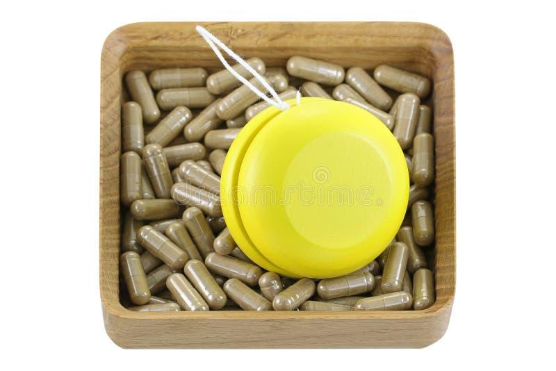 Una caja de madera por completo de medicinas herbarias con el yoyo amarillo imágenes de archivo libres de regalías