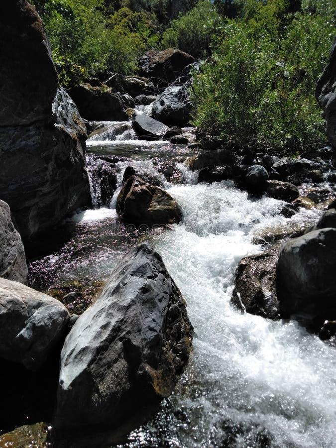 Una cala que fluye rápida acurrucada entre las montañas fotografía de archivo libre de regalías