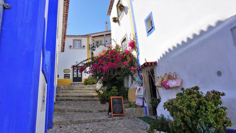 Una calle colorida en la ciudad medieval de Obidos, Portugal Obidos es una ciudad con historia y cultura Combina las Edades Media foto de archivo libre de regalías