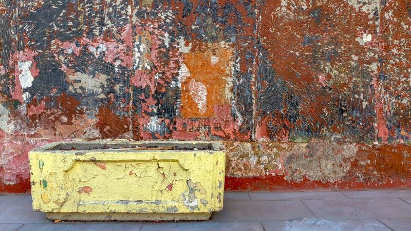 Una calle con una pared enyesada con una pintura multicolora vieja, enarenada y un macizo de flores amarillo vacío quebrado fotografía de archivo