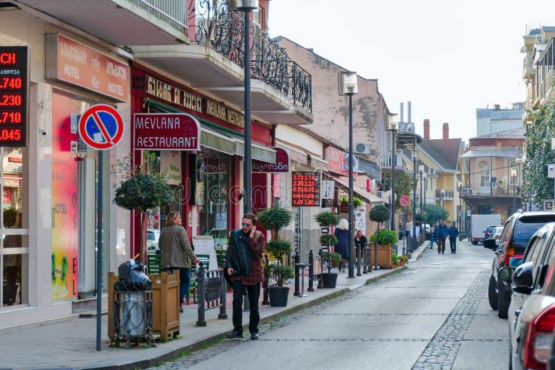 Una calle muy transitada acogedora de una pequeña ciudad con la gente, coches, restaurantes, cambiadores imagen de archivo