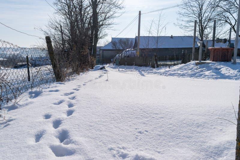 Una calle nevosa del pueblo con algunas huellas fotos de archivo