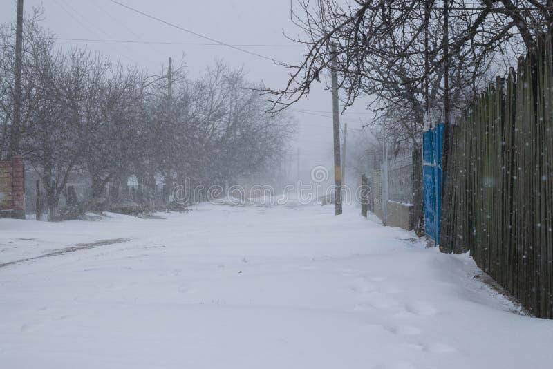 Una calle nevosa del pueblo durante una tormenta de la nieve fotos de archivo libres de regalías
