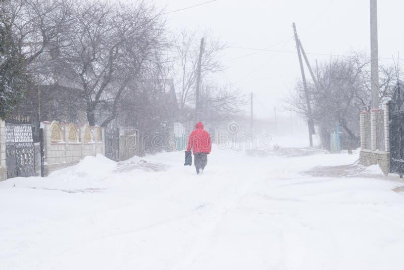 Una calle nevosa del pueblo durante una tormenta de la nieve y un hombre en una chaqueta roja fotos de archivo libres de regalías