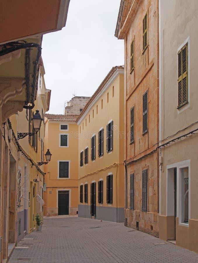 Una calle vacía reservada en menorca del ciutadella con los balcones sobresalientes y los edificios pintados amarillos y marrones foto de archivo