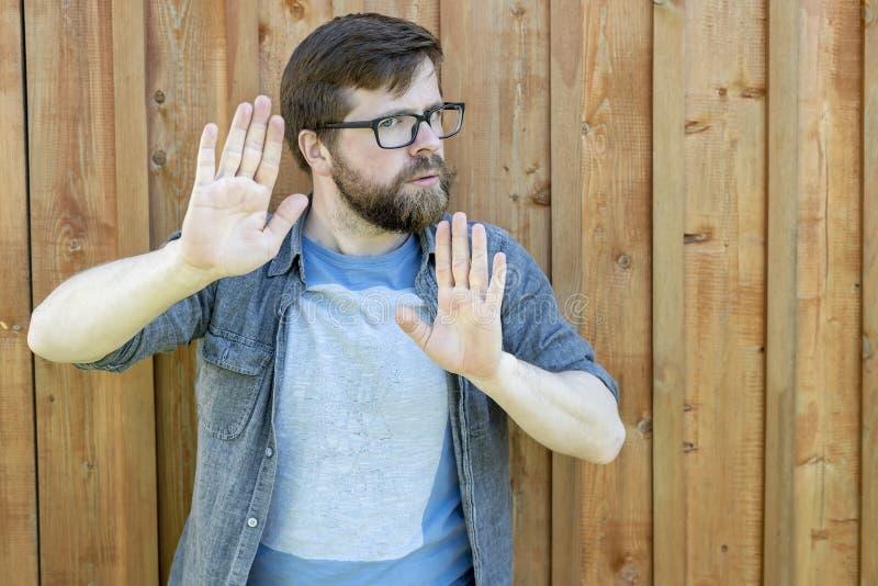 Una calma, un pus barbudo seguro de sí mismo del hombre sus palmas como una defensa o calmar alguien abajo y mirada en la cámara  foto de archivo libre de regalías