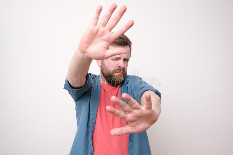 Una calma, uomo sicuro ha messo le sue palme in avanti come protezione e restrette un occhio Isolato su priorit? bassa bianca immagini stock