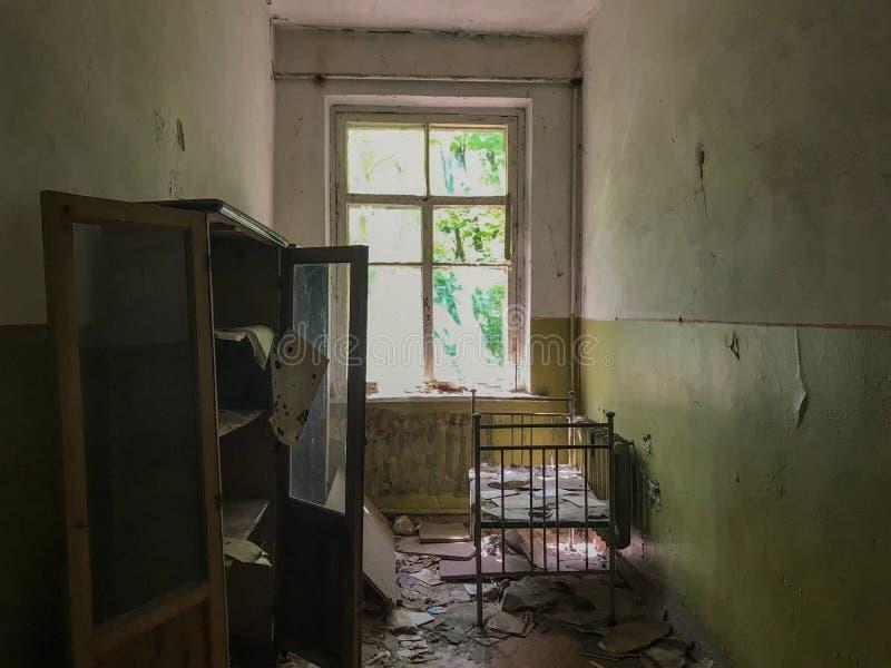 Una cama en una escuela abandonada en Pripyat, Ucrania cerca de Chernóbil foto de archivo