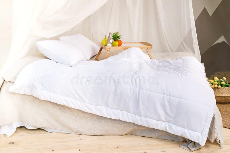 Una camera da letto accogliente nei colori pastelli con un pavimento di legno, un grande letto a baldacchino, il vassoio con frut immagini stock libere da diritti