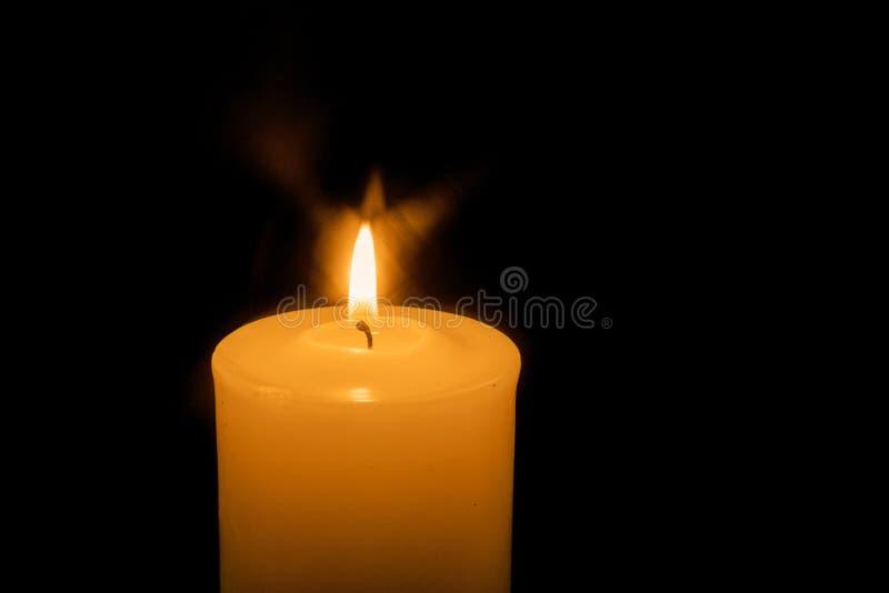 Una candela bruciante su fondo scuro fotografie stock libere da diritti